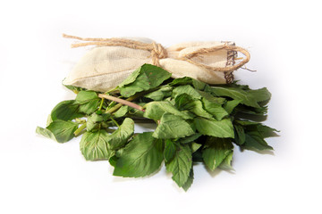 small pile of leaves mint and a canvas bag for spices