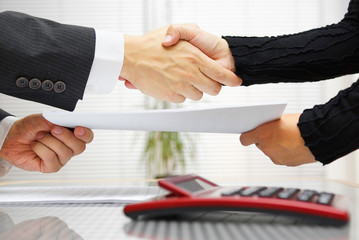 businesswoman and businessman are handshaking and exchanging con