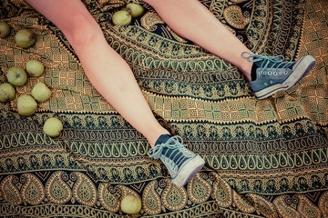 The legs of a woman surrounded by apples