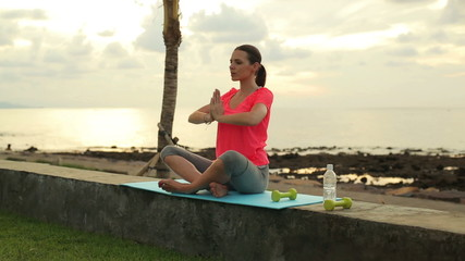 Attractive woman meditating by the sea in the evening