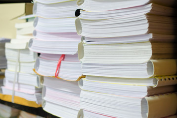 Pile of documents on desk stack up high waiting to be managed.