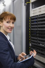 Pretty technician using tablet pc while working on servers
