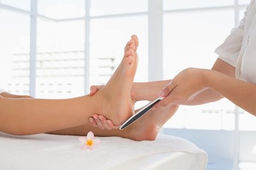 Side view of a young woman receiving pedicure treatment
