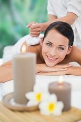 Brunette enjoying a herbal compress massage