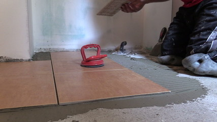 Construction worker place floor tiles. Home renovation