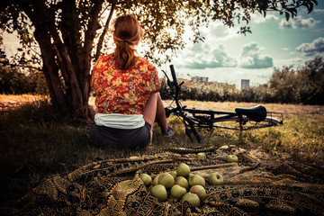 Young woman with apples and bicycle