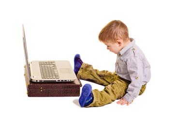 Cute little boy sitting before a laptop