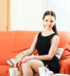 girl in black dress sitting on  sofa