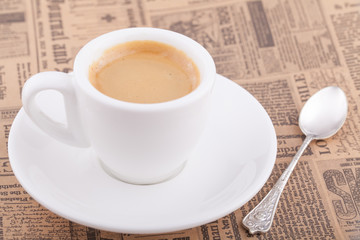 White cup of coffee on newspaper