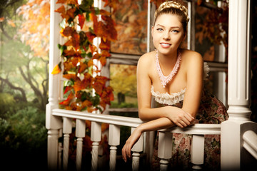 Young beautiful woman in vintage dress on autumn porch. Beauty g
