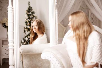 Beautiful young woman in white near the Christmas tree. Beautifu