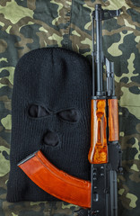 Ski mask and ak 47 on a camouflage background, close up