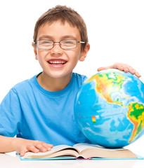 Little boy is examining globe