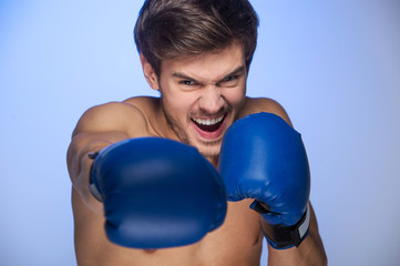 Handsome muscular young man wearing boxing gloves.
