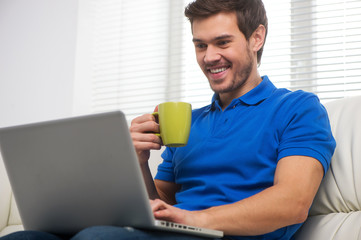 Young man happy on sofa with laptop.