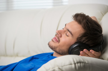 Man enjoying music lying on couch.