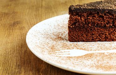 Piece of chocolate cake in a white plate with cocoa powder