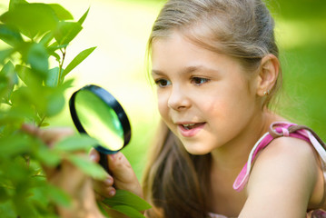 Girl is looking at tree leaves through magnifier