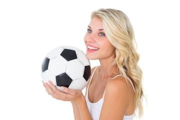 Pretty blonde football fan holding ball