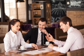 Three friends discuss graph lying on table at cafe.