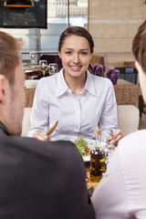 Young woman eating mixed vegetable salad in cafe.