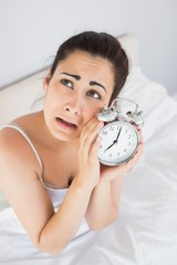 Annoyed woman holding an alarm clock in bed