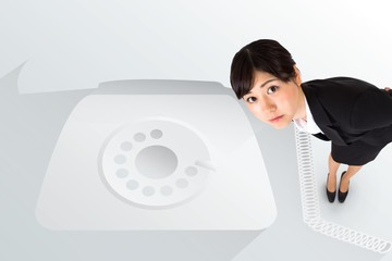 Serious businesswoman bending against retro telephone