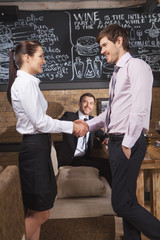 Young attractive businessman and businesswoman at cafe.