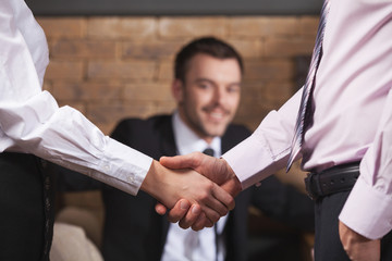 Business people shaking hands after meeting in cafe.