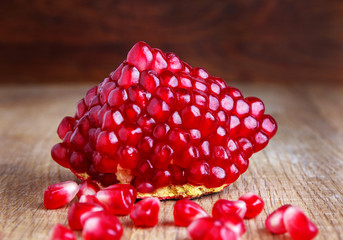 Piece of pomegranate on wood