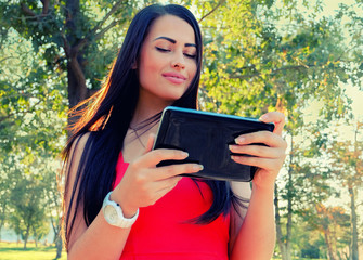 Female student using her tablet-pc outdoors.