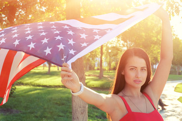Serious  young woman holding american flag