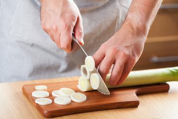 chef chopping leek in kitchen