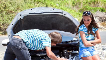 Man and woman near their broken car.
