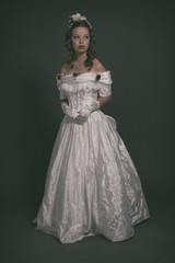 Victorian fashion woman wearing white dress. Studio shot against