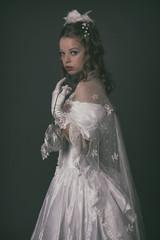 Victorian fashion woman wearing white dress. Holding handbag. St
