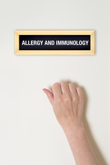 Female hand is knocking on Allergy and Immunology door