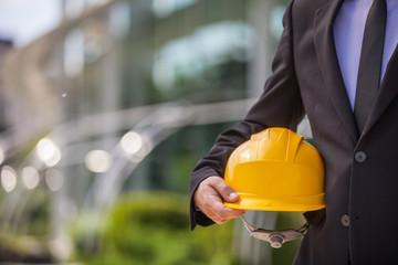 professional engineer holding yellow helmet.