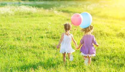 happy girls twin sisters  with balloons in summer