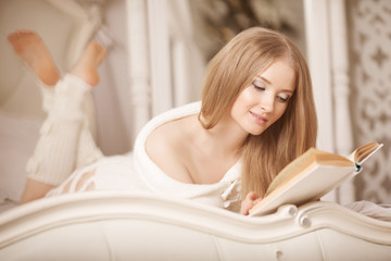 Girl reading book. Beautiful young woman lying on the sofa readi