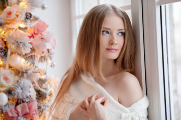 Beautiful young woman in white near the Christmas tree. Beautifu