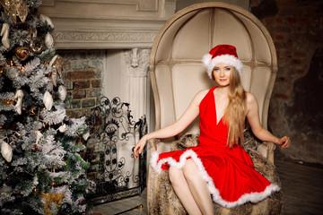 Young beauty smiling santa woman near the Christmas tree. Fashio
