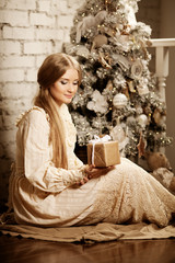 Young luxuy vintage woman near Christmas tree with gift. Beautif