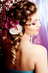 Makeup, hairstyle. Young beautiful woman with luxurious hair. Mo