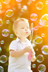 Child blowing a soap bubbles. Boy playing. Kid blowing bubbles o