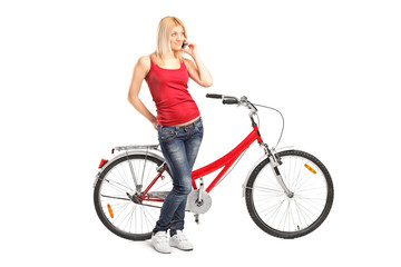 Woman talking on phone and standing by a bike