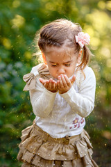 Little girl blows gold glitter from his hands.