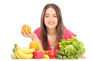 Woman posing behind fruits and vegetables