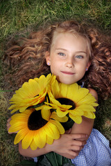 Cheerful and charming young girl with sunflowers on grass