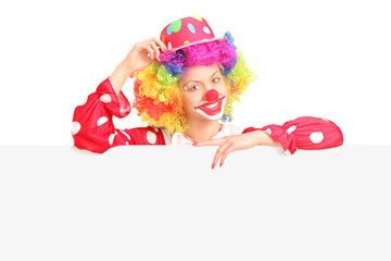 Female clown standing behind a blank panel
